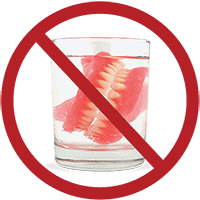 Old-fashioned dentures in a glass of water